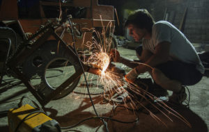 "Danilo Baletic, 22, performs last minute work on scrap metal parts for his sculpture at junkyard in Podgorica, July 22, 2014. Baletic makes sculptures of his childhood cartoon heroes ""Transformers"" from scrap metal. In the last two years, he has made seven ""Transformers"" that are placed on the streets of Montenegro's capital Podgorica as part of an exhibition called ""Transformers defending Podgorica"".  Picture taken July 22, 2014. REUTERS/Stevo Vasiljevic (MONTENEGRO  - Tags:  SOCIETY) - RTR3ZW57"